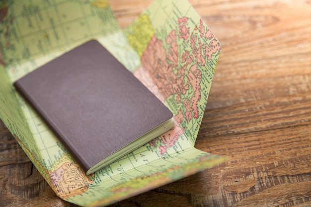 Passport on top of a world map Free Photo