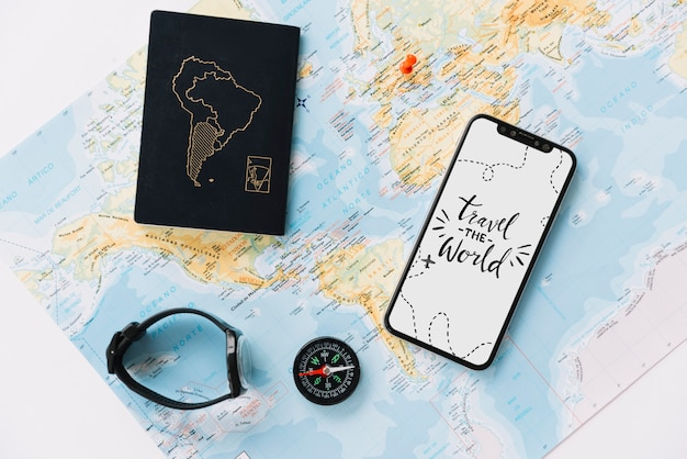 Passport; wrist watch; compass and mobile phone with travel message on white screen Free Photo
