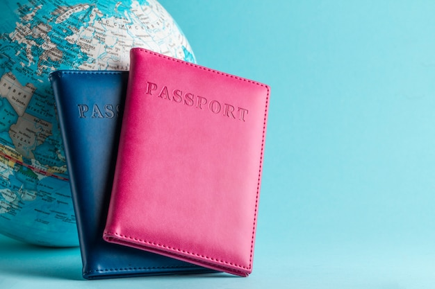Паспорта и глобус на синем фоне. путешествия, отдых, отдых. отдых, туризм, путешественник. Premium Фотографии