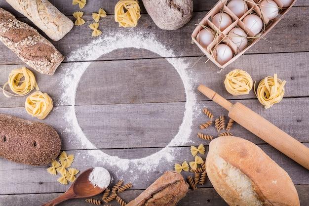 Макаронные изделия и хлеб на деревянных фоне. вид сверху с копией пространства. ингредиенты для хлебобулочных изделий Premium Фотографии