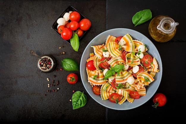 トマト、モッツァレラチーズ、バジルのパスタ色のファルファッレサラダ。 無料写真