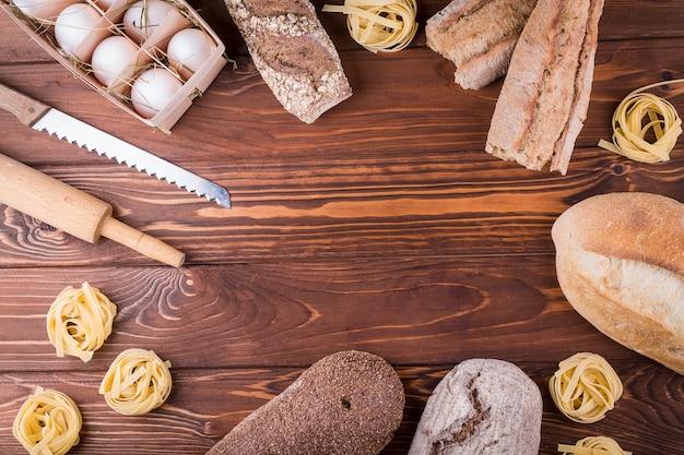 Макаронные изделия, яйца и хлеб на деревянных фоне. вид сверху с копией пространства. ингредиенты для хлебобулочных изделий Premium Фотографии