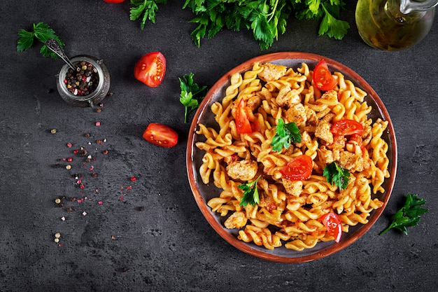 Pasta fusilli with tomatoes, chicken meat and parsley on plate on dark table Premium Photo