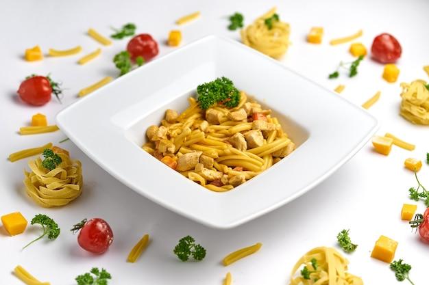 鶏肉のトマトソースパスタ、木の板にパセリで飾られたトマト Premium写真