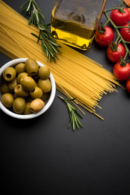Pasta and ingredients for cooking on dark background Free Photo