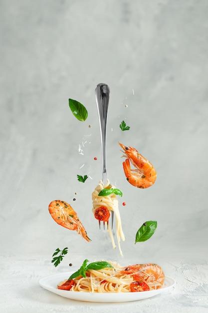 Лингвини из макаронных изделий с креветками и вилкой, пролетая над блюдом. творческий натюрморт. концепция итальянской кухни Premium Фотографии