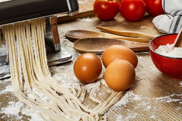 Паста-машина с лапшой и ингредиентами на деревянном столе Premium Фотографии