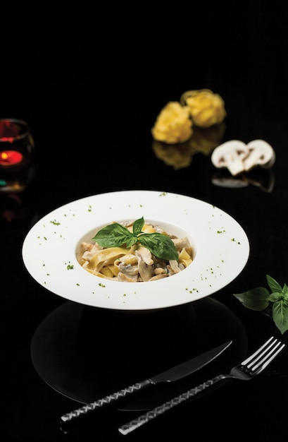 Pasta noodles in cream sauce with basilic leaves. Free Photo