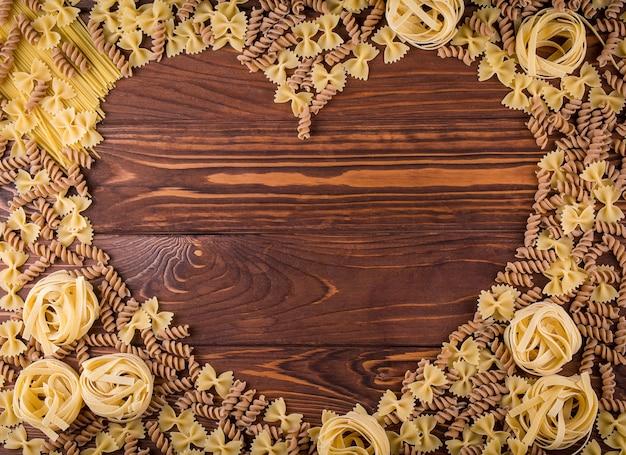 Макаронные изделия на деревянных фоне. вид сверху с копией пространства. ингредиенты для хлебобулочных изделий. Premium Фотографии