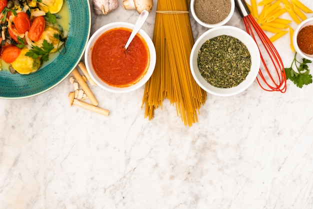 Pasta and pasta ingredients on marble textured backdrop Free Photo
