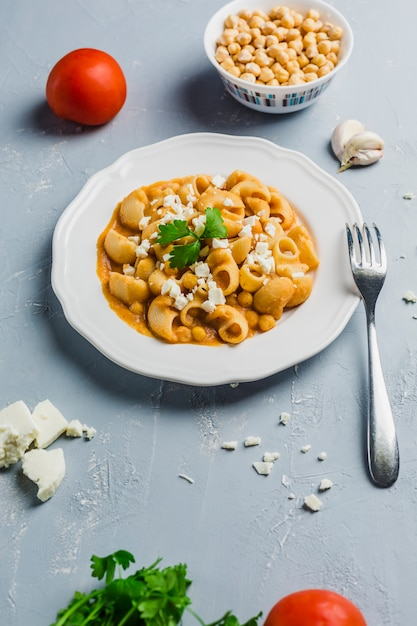 Pasta pipa the rigat with a sauce of chickpeas and tomatoes, sprinkled with feta cheese and cilantro Premium Photo