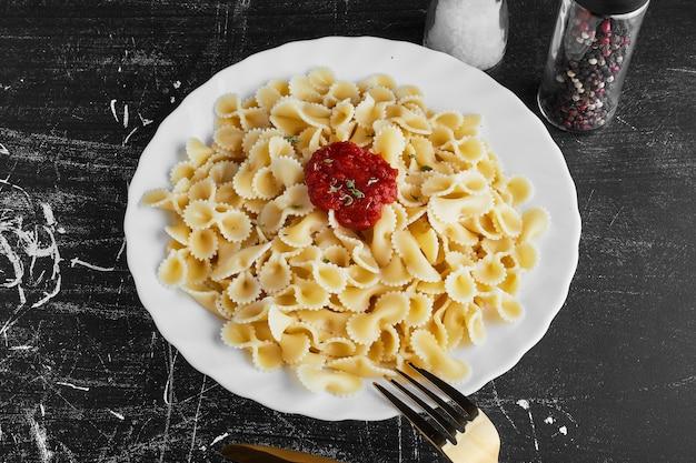 Pasta in salsa di peperoncino rosso in un piatto bianco. Foto Gratuite
