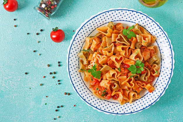 Pasta in the shape of hearts with chicken and tomatoes in tomato sauce. top view Free Photo
