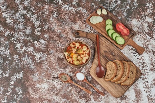 周りに野菜の盛り合わせが入ったパスタスープ 無料写真