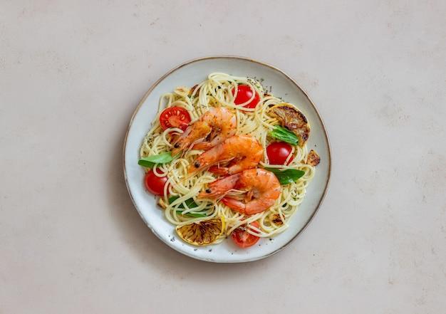 새우, 토마토, 마늘, 시금치, 레몬을 곁들인 파스타 스파게티. 이탈리아 요리. 해물. 다이어트. 프리미엄 사진