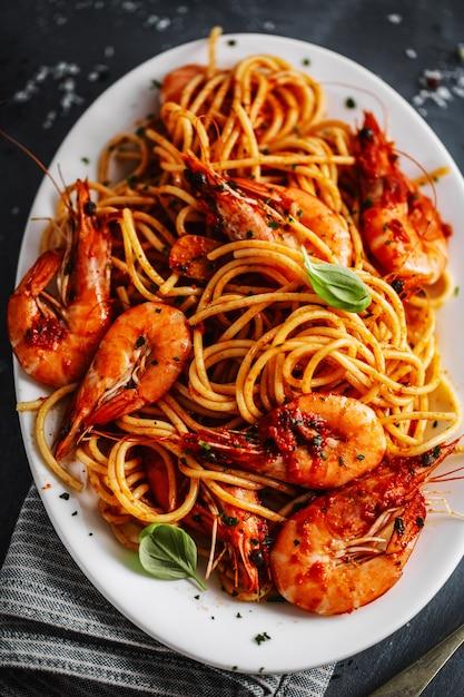 Gli spaghetti della pasta con i gamberetti e la salsa al pomodoro sono servito sul piatto su superficie scura. avvicinamento. Foto Gratuite