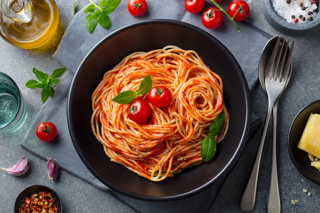 Pasta, spaghetti with tomato sauce in black bowl. top view. Premium Photo