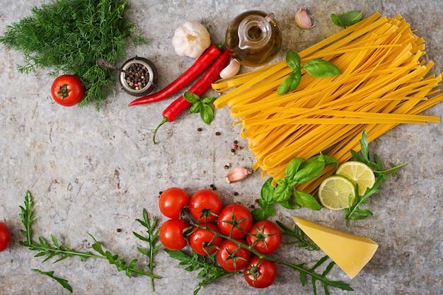 パスタタリアテッレと料理の材料(トマト、ニンニク、バジル、チリ)。上面図 Premium写真