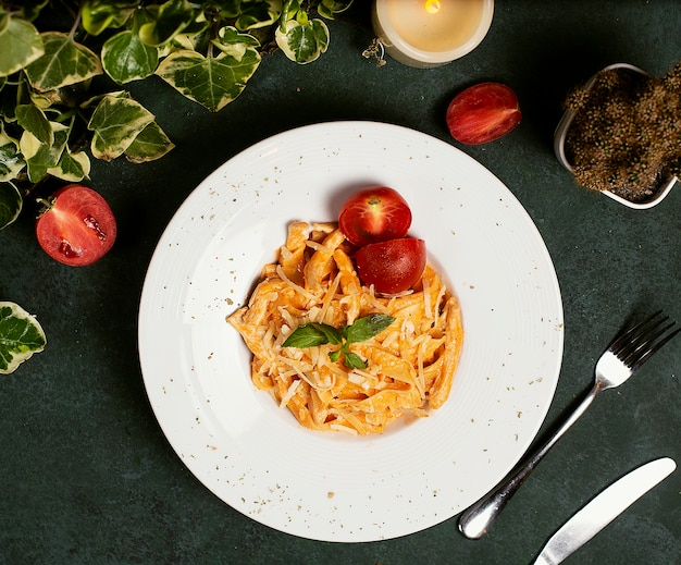 Pasta in tomato sauce with chopped parmesan , tomato and basilic Free Photo