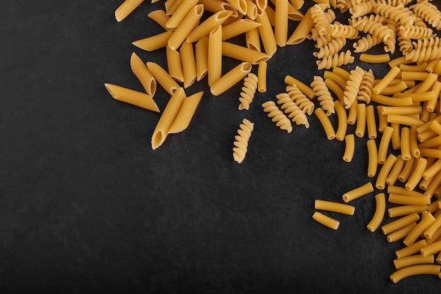 黒の背景に食料品ストックのパスタの品種。 無料写真
