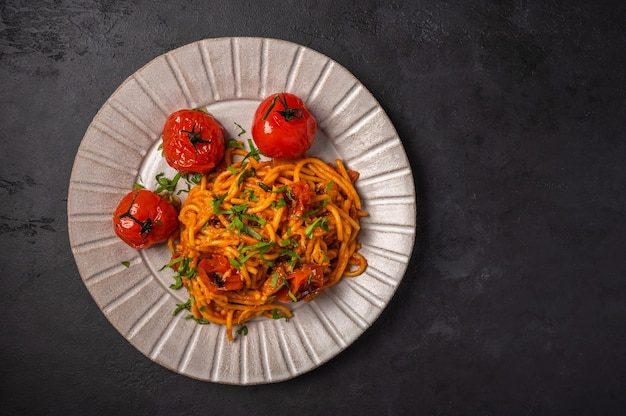 Pasta with baked cherry tomatoes, cheese and parsley on a dark textured background, top view, copy Premium Photo