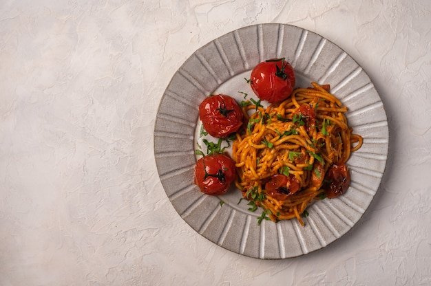 Pasta with baked cherry tomatoes, cheese and parsley on light background, top view, copy space Premium Photo