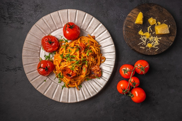 Pasta with baked cherry tomatoes, parmesan and pesto sauce on dark graphite background, top view, copy space Premium Photo
