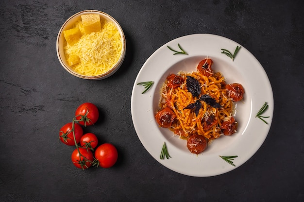 Pasta with baked tomatoes, grated parmesan and pesto sauce in ceramic bowls on dark graphite background, top view, copy space Premium Photo