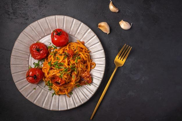 Паста с помидорами черри, сыром и чесноком подается на тарелке на темном текстурированном фоне, вид сверху Premium Фотографии