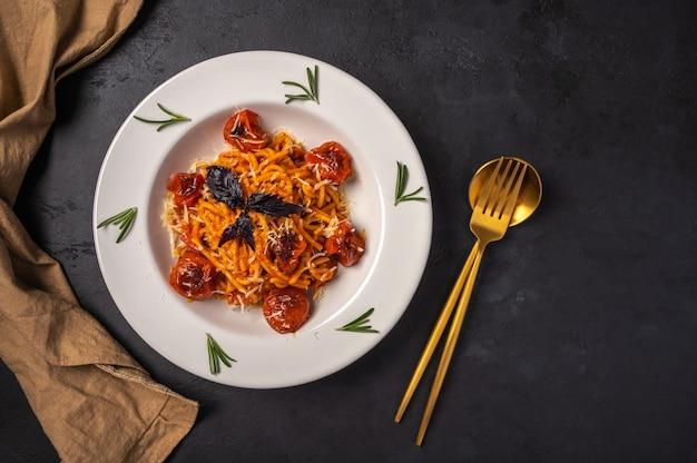 Паста с помидорами черри, сыром и розмарином подается на тарелке с ложкой, вилкой и салфеткой на темноте Premium Фотографии