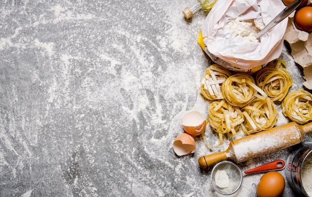 Паста с ингредиентами - мукой, яйцами и разными инструментами для приготовления. на каменном столе. свободное место для текста. вид сверху Premium Фотографии