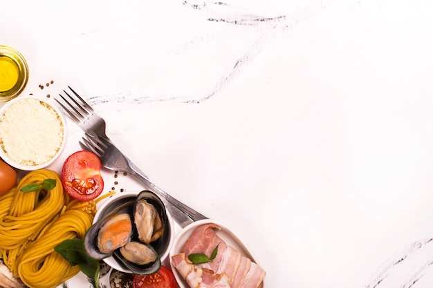 Pasta with ingredients over white marble table Premium Photo