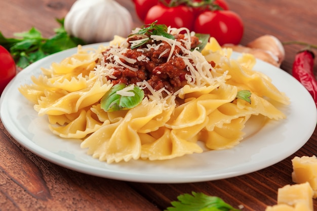 Pasta with meat, tomato sauce and vegetables on the table Premium Photo