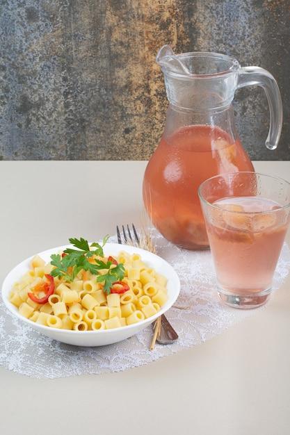 白いボウルとレモネードにパセリとトマトのスライスが入ったパスタ 無料写真