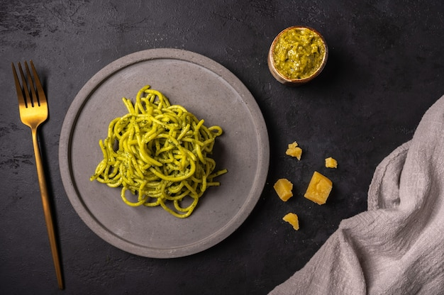 Pasta with pesto and parmesan, served on gray ceramic plate and golden fork on dark textured backgroun, top view Premium Photo