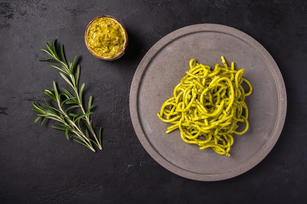 Pasta with pesto and rosemary, served on gray ceramic plate on dark textured background, selective focus, top view, copy space Premium Photo