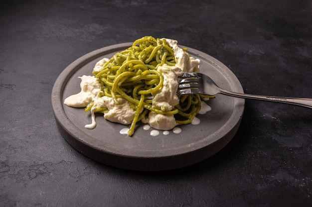 Pasta with pesto and stracatella, served on gray ceramic plate and fork on dark textured backgroun, selective focus, top view Premium Photo
