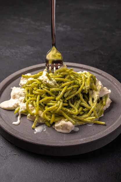 Pasta with pesto and stracatella, served on gray ceramic plate and fork on dark textured backgroun, vertical view, selective focus Premium Photo