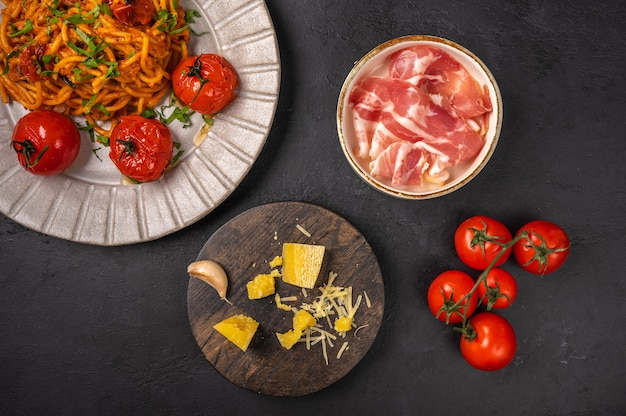 Pasta with prosciutto ham, cherry tomatoes, parmesan and pesto sauce on dark graphite background, top view, copy space Premium Photo