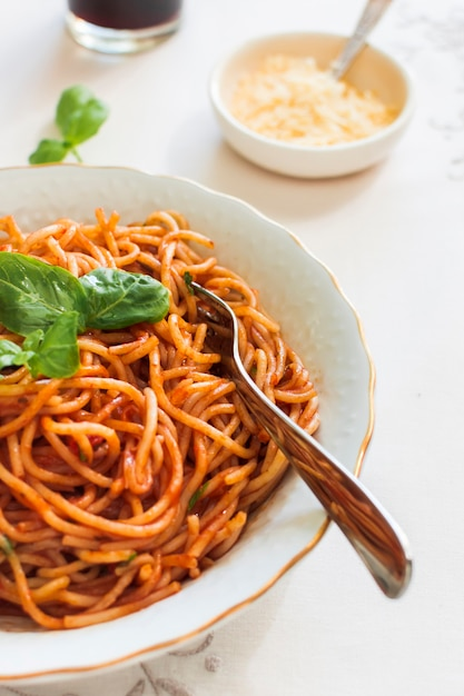 Pasta with tomato sauce and basil on ceramic plate with fork Free Photo