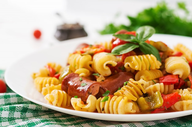 Pasta with tomato sauce with sausage, tomatoes, green basil decorated in white plate on a wooden table. Free Photo