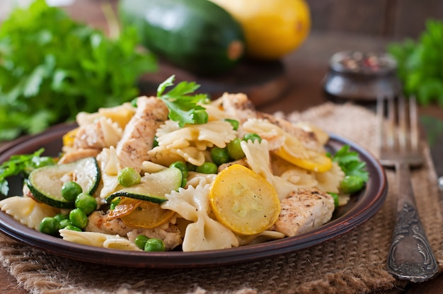 Pasta with zucchini, chicken and green peas Free Photo