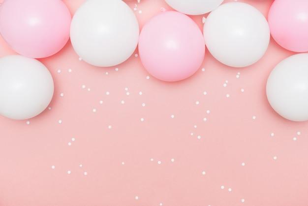 Pastel balloons and white confetti on pink Premium Photo