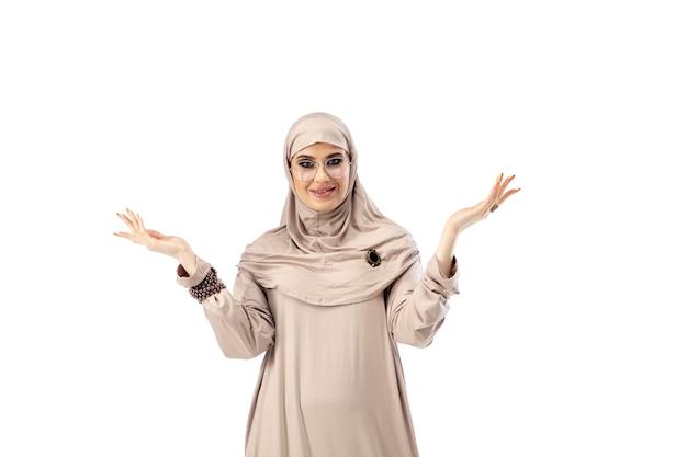 파스텔. 고립 된 세련 된 Hijab에서 포즈 아름 다운 아랍 여자 패션, 뷰티, 스타일 개념. 트렌디 한 메이크업, 매니큐어 및 액세서리가있는 여성 모델. 무료 사진