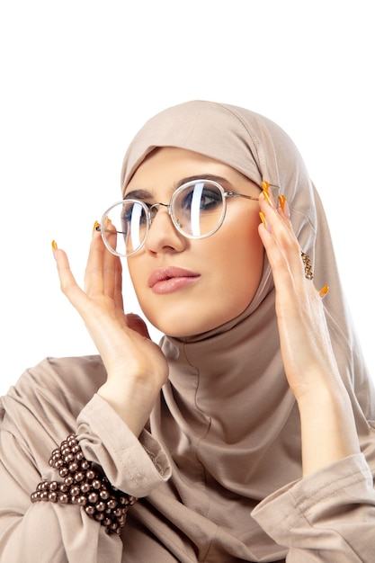 Pastel. beautiful arab woman posing in stylish hijab isolated on  wall with . fashion, beauty, style concept. female model with trendy make up, manicure and accessories. Free Photo