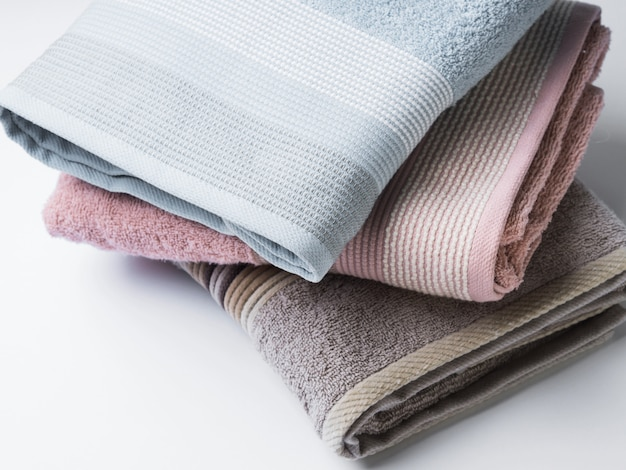 Pastel color clean folded towels on white Premium Photo
