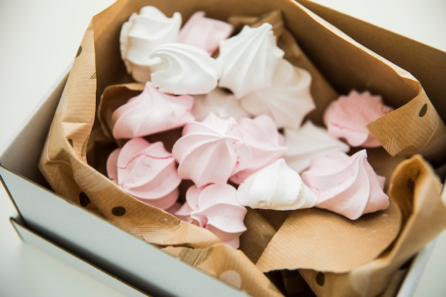 Pastel colored zephyrs wrapped in the paper inside the open box Free Photo