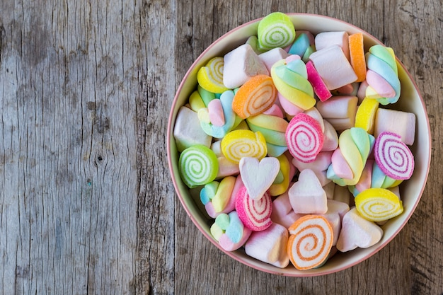 Pastel and colorfu of marshmallow and gummy candy in a wooden bowl on wooden table. Premium Photo