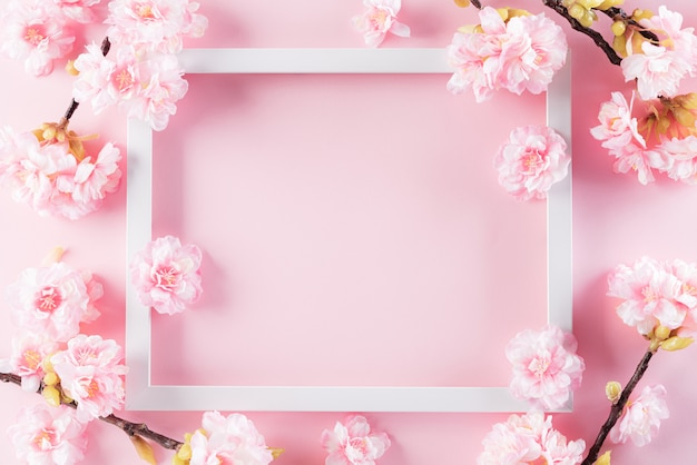 Pastel pink colours background with picture frame and blossom flowers flat lay patterns. Premium Photo