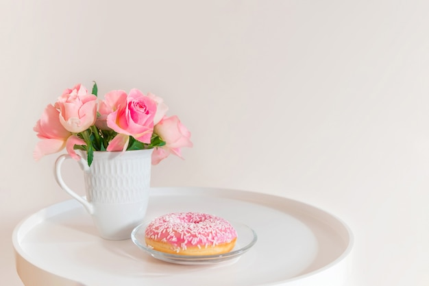 Pastel pink roses in white cup with pink donut on white coffee table Premium Photo